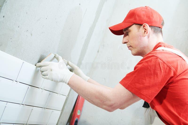 安装地铁瓦片的铺磁砖工在墙壁 在家户内整修 图库摄影