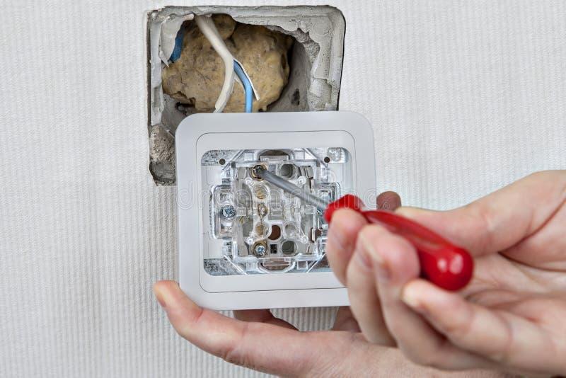 安装墙壁灯开关,连接到电子接线,拉紧 免版税库存照片