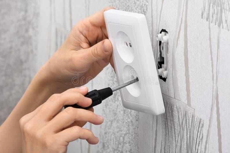 安装墙壁电源插座的手 图库摄影