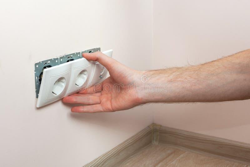 安装墙壁电源插座的电工的手 免版税库存图片