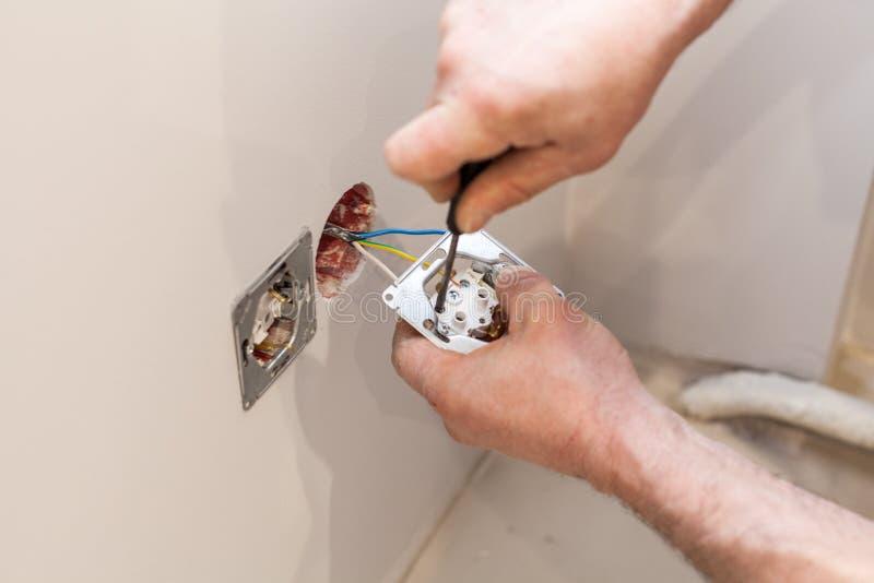 安装墙壁电源插座的电工的手 免版税库存照片