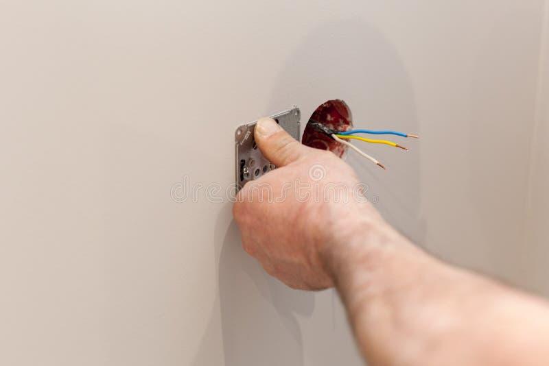 安装墙壁电源插座的电工的手 图库摄影