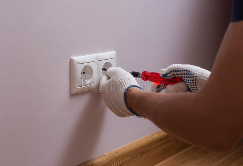 安装墙壁电源插座,照片的关闭的电工 免版税库存图片