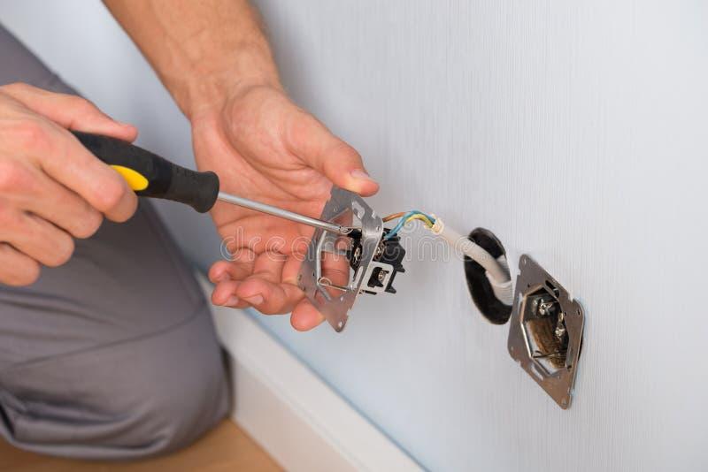 安装壁上插座的电工手 免版税库存图片