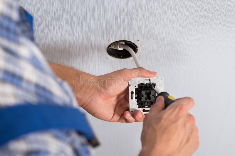 安装壁上插座的电工手 库存照片