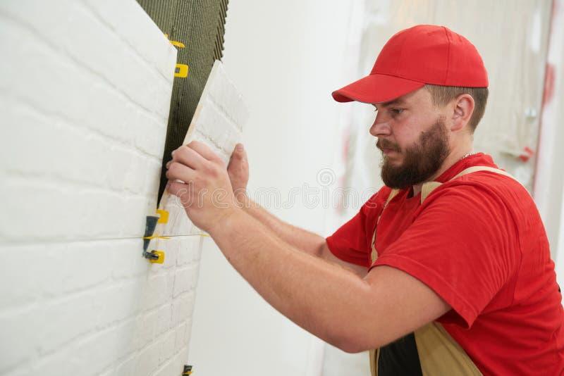 安装大号瓦片的铺磁砖工在墙壁 在家户内整修 免版税库存图片