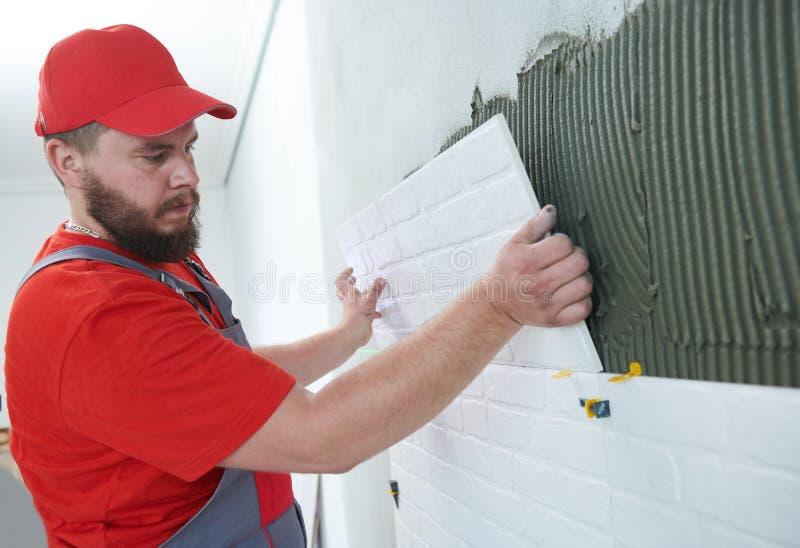安装大号瓦片的铺磁砖工在墙壁 在家户内整修 库存照片