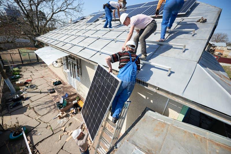 安装太阳光致电压的盘区系统在房子屋顶  免版税库存照片