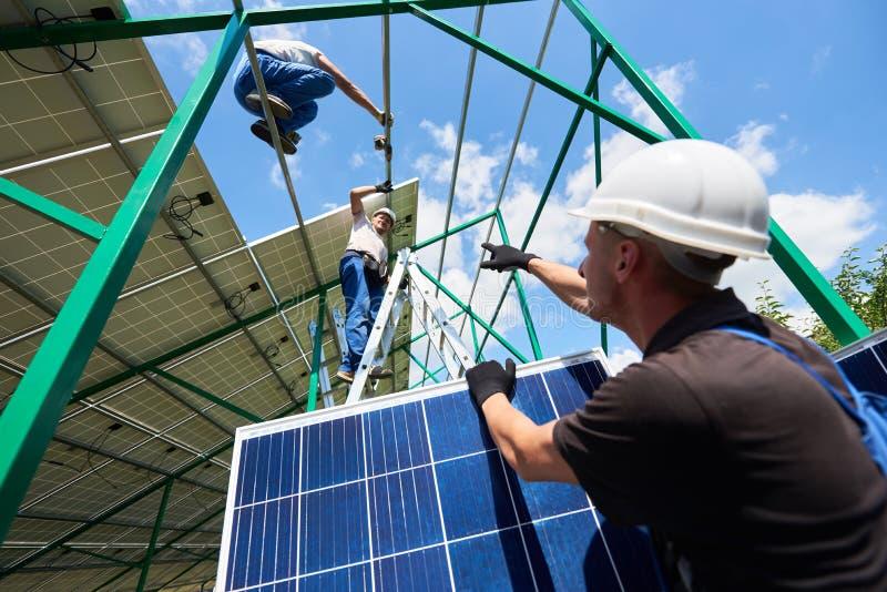 安装太阳电池板的专业工作者在绿色金属建筑 库存图片