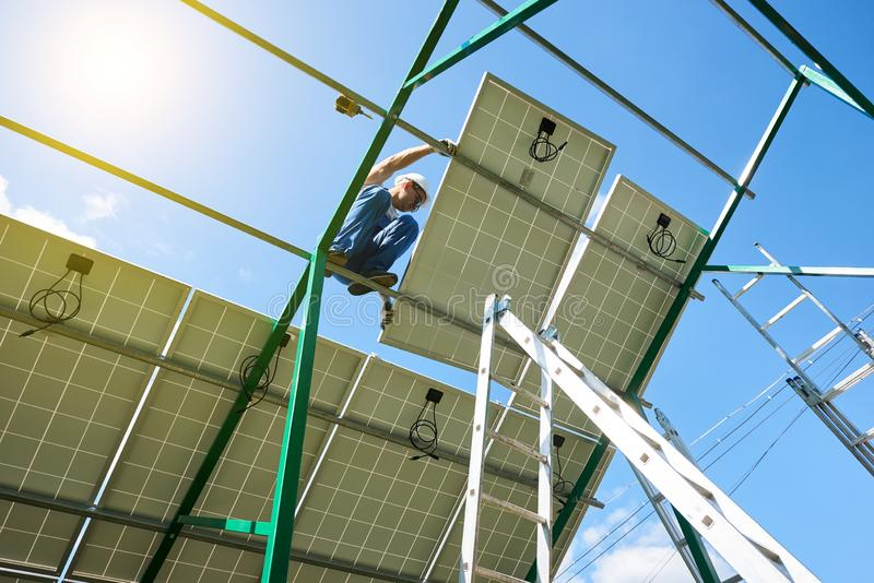 安装太阳电池板的专业工作者在绿色金属建筑 免版税库存图片