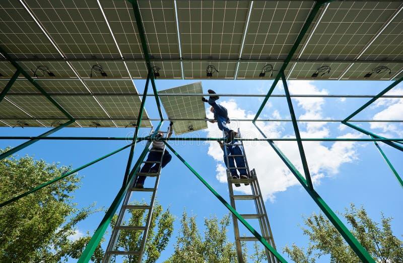 安装太阳电池板的专业工作者在绿色金属建筑 免版税库存照片