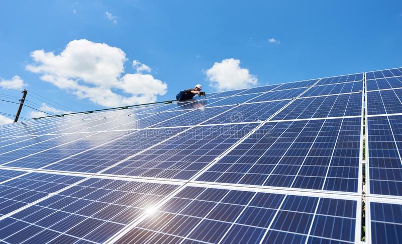 安装太阳电池板的专业工作者在绿色金属建筑 库存照片