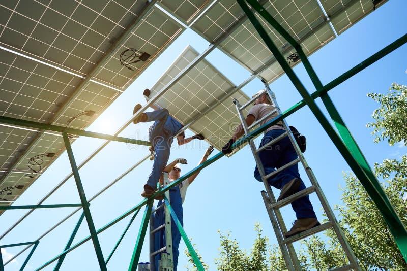 安装太阳电池板的专家在绿色金属建筑 免版税库存照片
