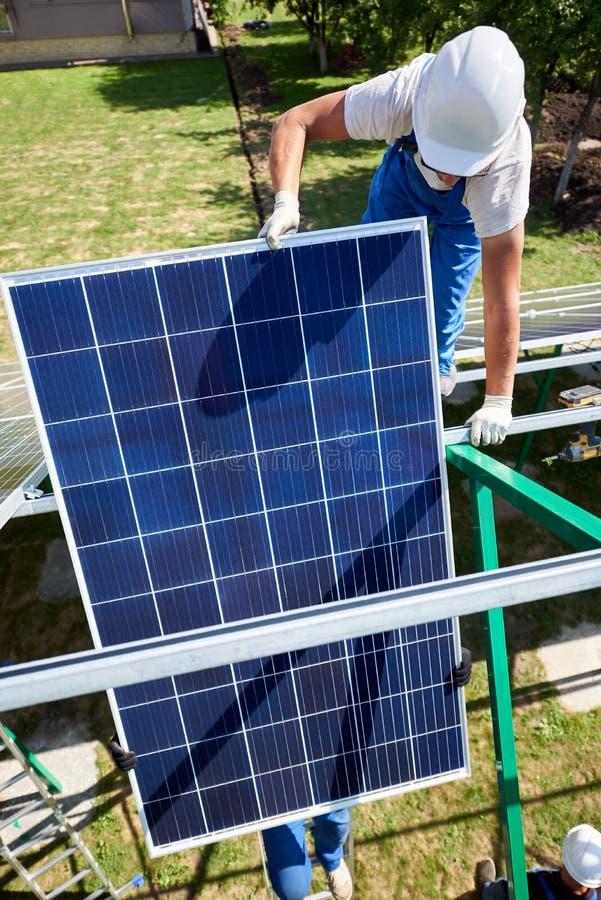 安装太阳电池板的两mounters在绿色金属尸体 免版税库存图片