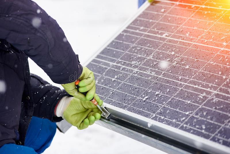 安装太阳电池板的工作者的手在多雪的天气 特写镜头 库存照片