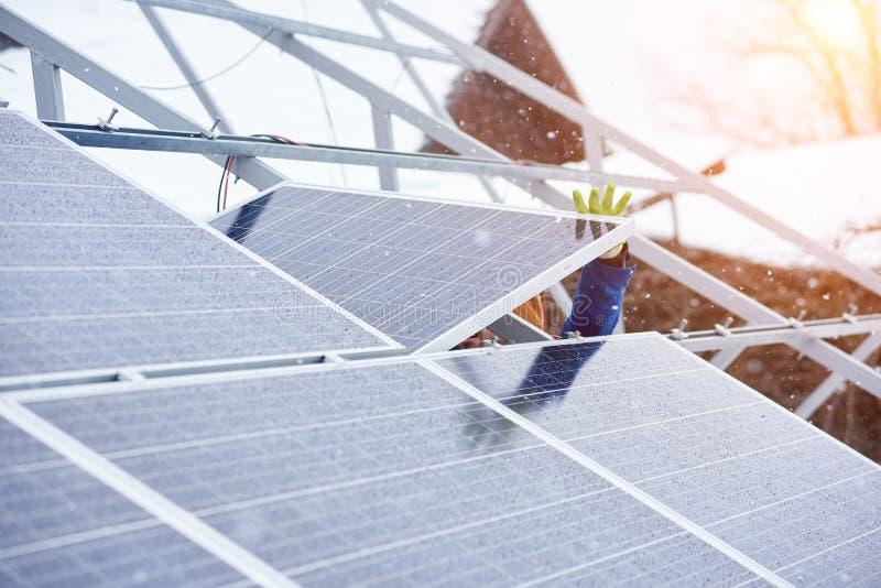 安装太阳电池板的过程在多雪的天气在冬天 免版税图库摄影
