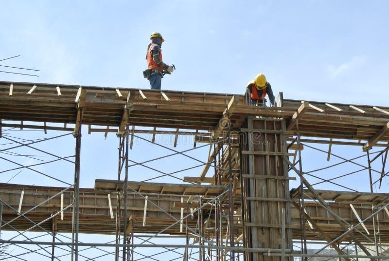 安装射线模板的建筑工人 免版税库存照片