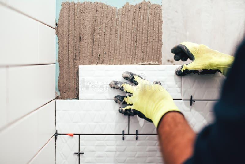 安装小陶瓷砖在卫生间墙壁和应用与修平刀的建筑工人灰浆 库存照片