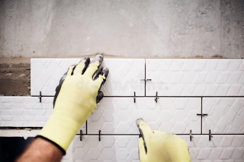 安装小陶瓷砖的产业工人在卫生间在改造工程期间 库存图片