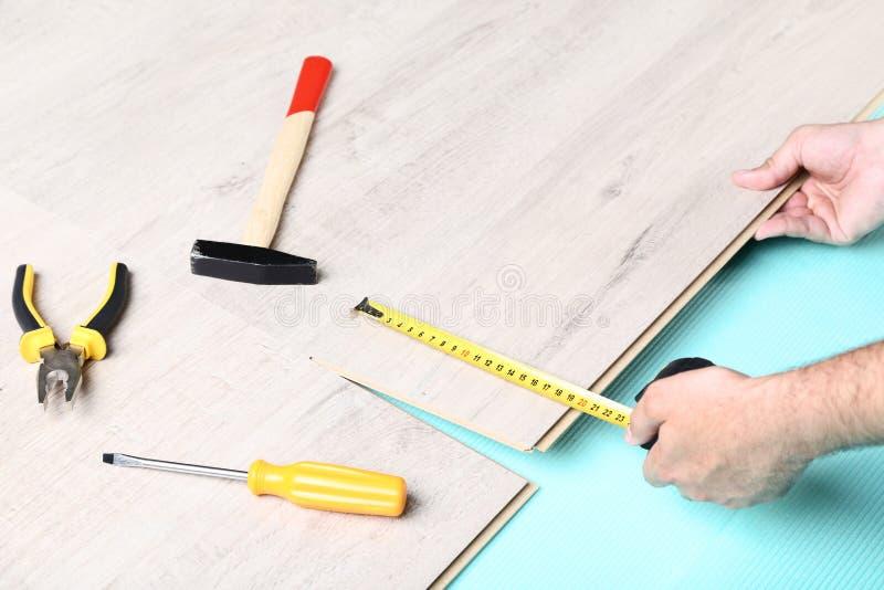 安装层压制品的地板的人 免版税库存图片