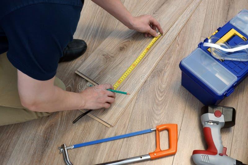 安装层压制品的地板的工作者 家庭概念的整修 图库摄影