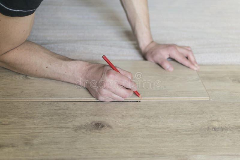 安装层压制品的地板的木匠工作者在屋子里 图库摄影