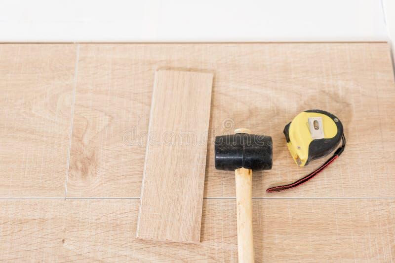 安装层压制品的木条地板在内部 在地板谎言不同的木匠工具上 锤子和评定的磁带 概念 库存照片