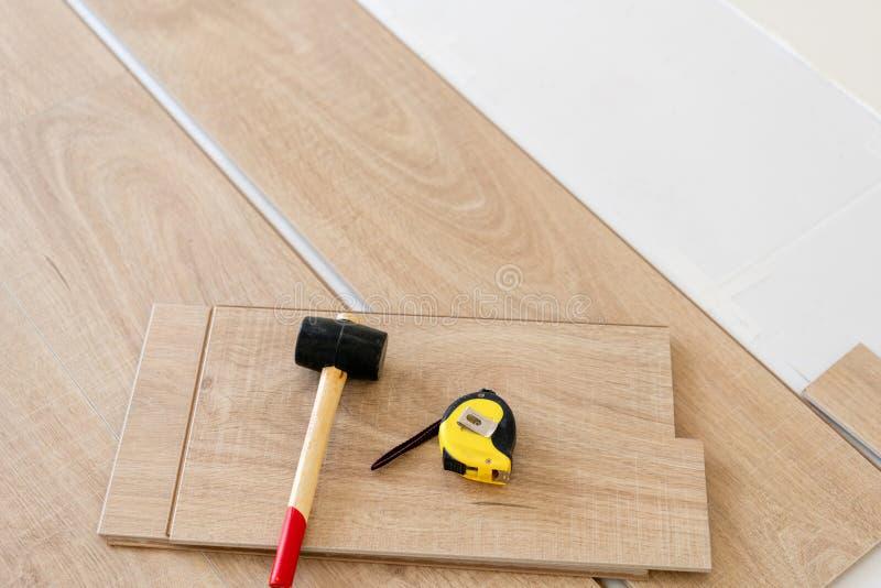 安装层压制品的木条地板在内部 在地板谎言不同的木匠工具上 锤子和评定的磁带 概念 免版税图库摄影