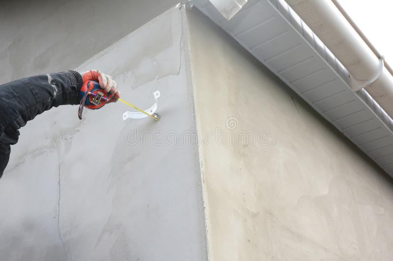 安装屋顶天沟水落管管子的承包商持有人 免版税库存图片