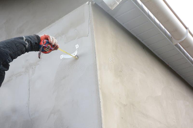 安装屋顶天沟水落管管子的承包商持有人 库存图片