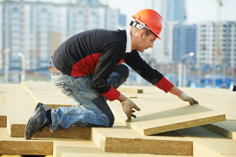 安装屋顶绝缘材料的屋面防水工工作者 库存图片