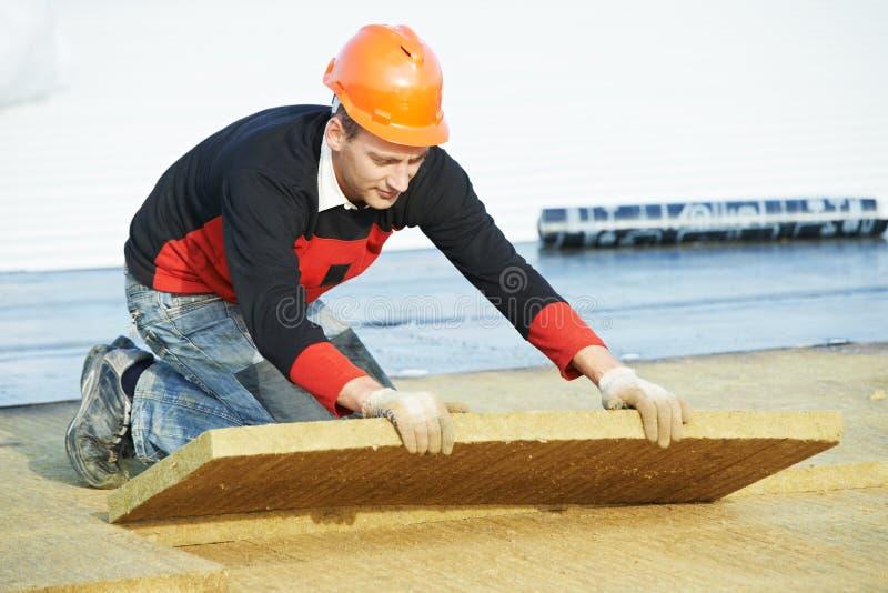 安装屋顶绝缘材料的盖屋顶的人工作者 库存图片