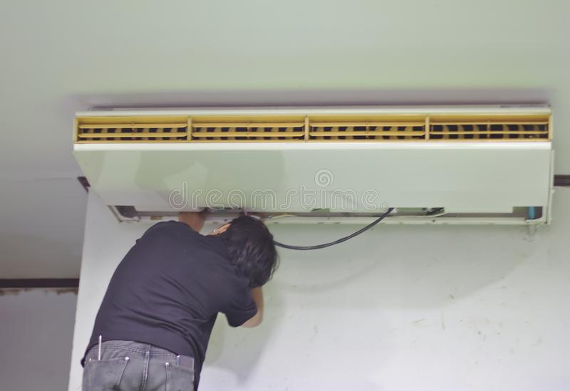 安装工修理在天花板的空调 在白色墙壁背景后打开空调盖子  免版税库存图片