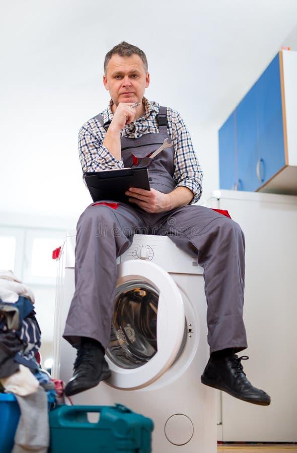 安装工修理在白色背景的一台洗衣机 库存照片