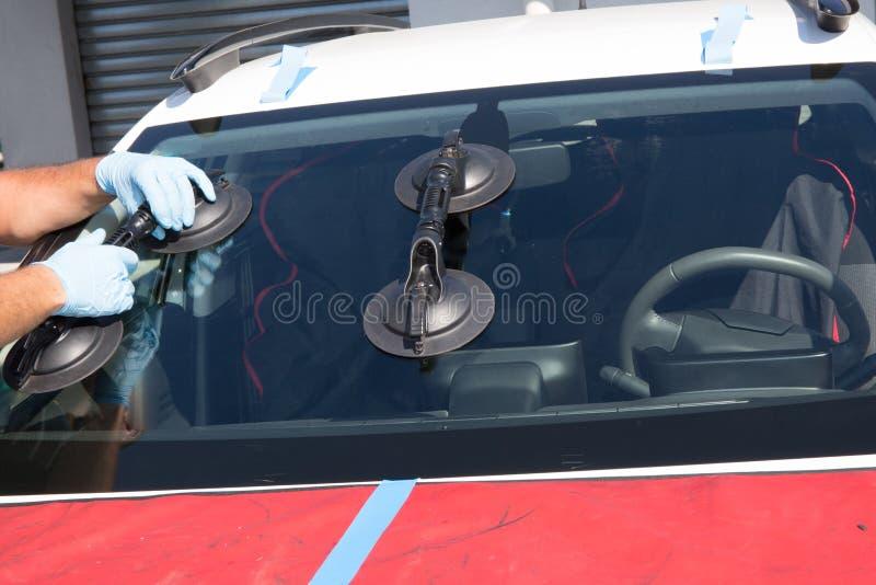 安装工修理汽车的挡风玻璃 免版税库存照片