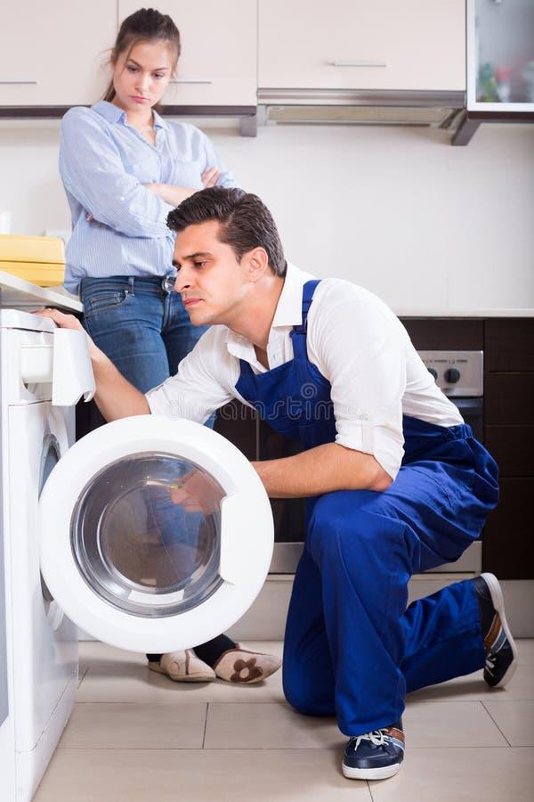 安装工和妇女在洗衣机附近 免版税库存照片