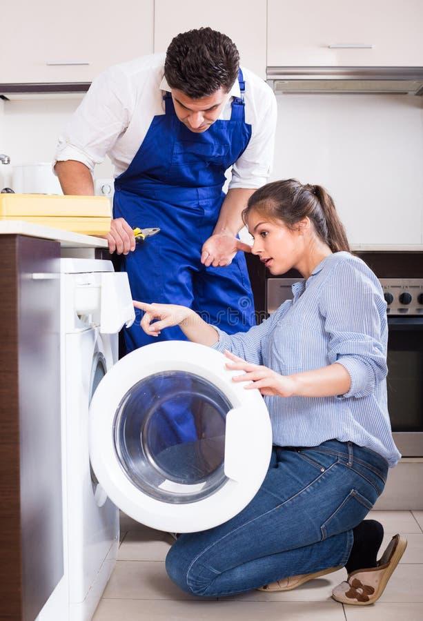 安装工和妇女在洗衣机附近 库存图片