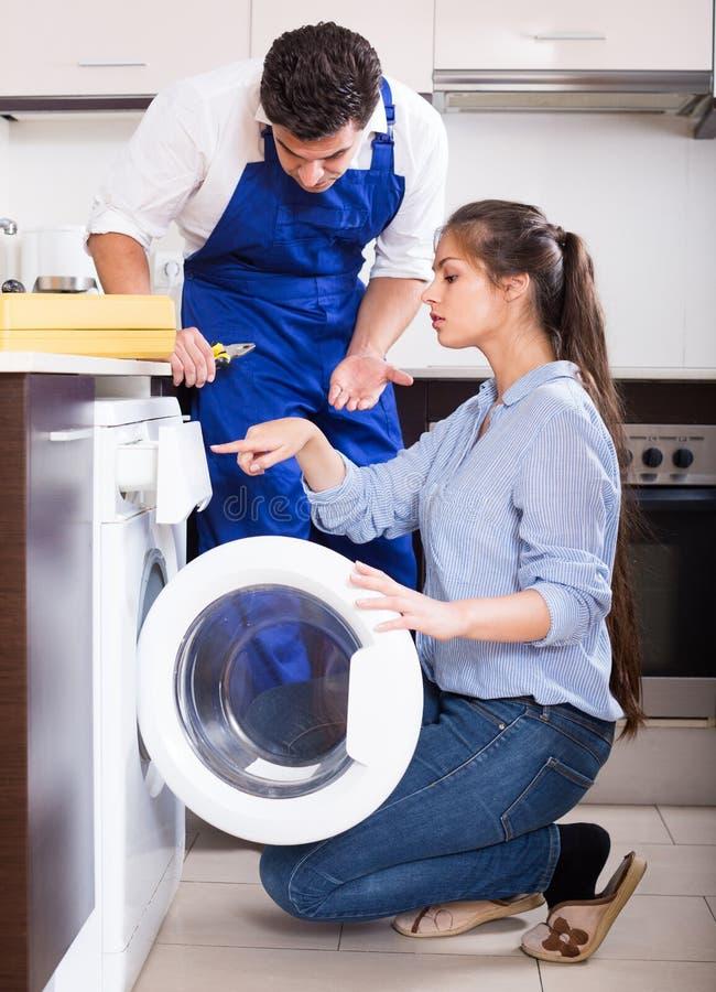 安装工和妇女在洗衣机附近 库存照片