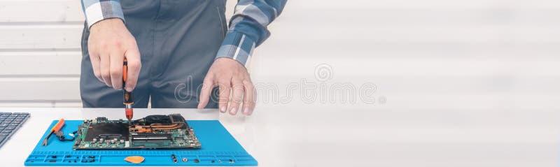 安装工在技术支持工作,参与膝上型计算机的恢复和清洁 库存照片