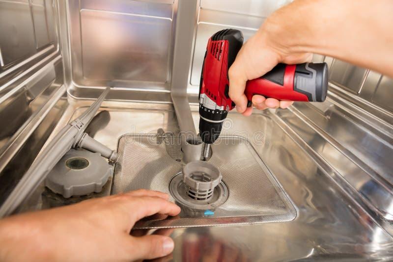 安装工定象洗碗机特写镜头  库存照片