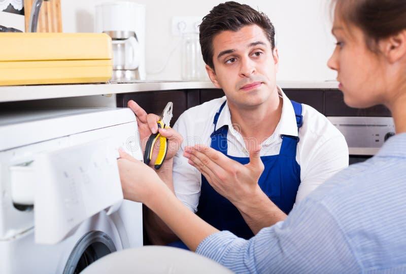 安装工解释的妇女如何使用洗衣机 免版税库存照片