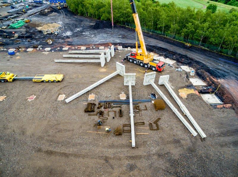 安装巨大的钢筋混凝土堆的巨大的起重机鸟瞰图在工地工作 免版税库存照片