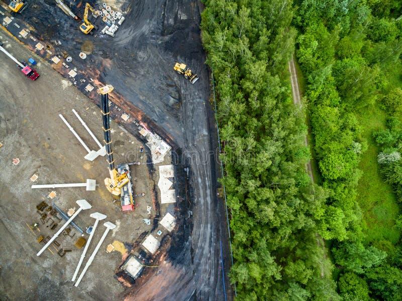 安装巨大的钢筋混凝土堆的巨大的起重机鸟瞰图在工地工作 免版税库存图片