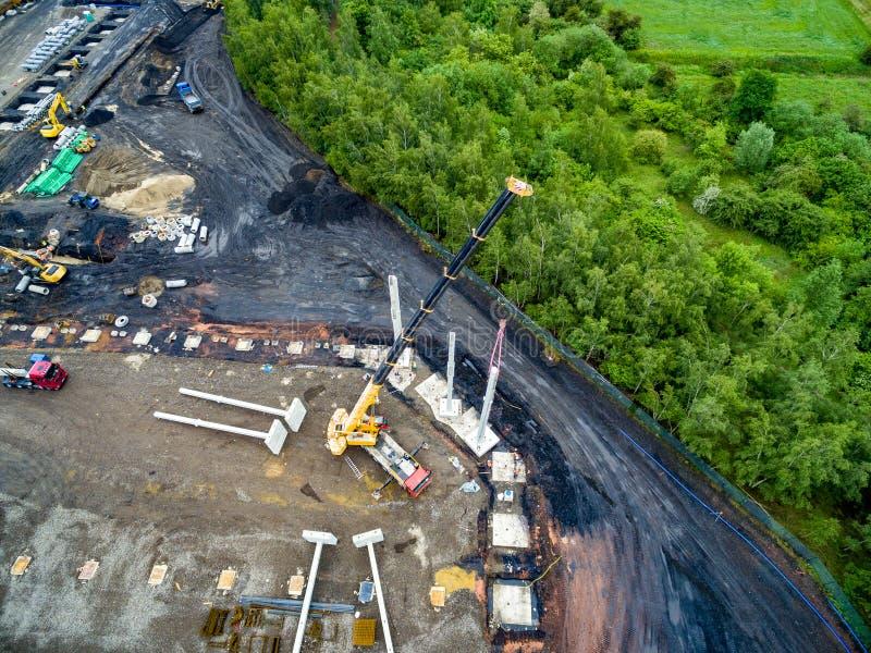 安装巨大的钢筋混凝土堆的巨大的起重机鸟瞰图在工地工作 库存照片