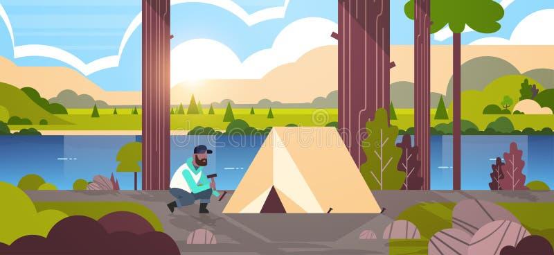 安装帐篷的非裔美国人的人徒步旅行者露营车为野营的远足的概念日出风景自然河做准备 皇族释放例证