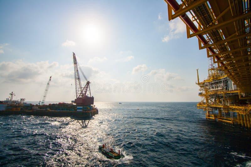 安装平台的大起重机船近海处,做海洋抬举费力的设施的起重机驳船在海湾运转 库存照片