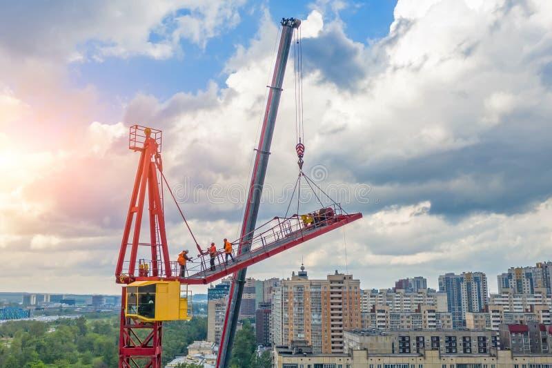 安装建筑用起重机的三角帆使用另一台起重机在卡车,登山人建造者的工作在高度, 库存图片