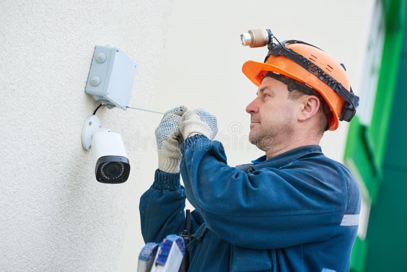 安装录影监视器的技术员工作者在墙壁 免版税图库摄影