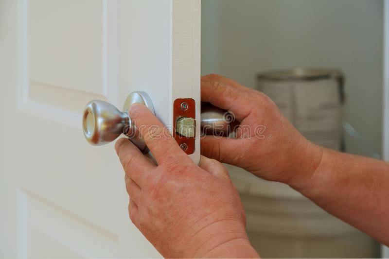 安装或修理一把新的deadbolt锁的一位专业锁匠的特写镜头 免版税库存图片