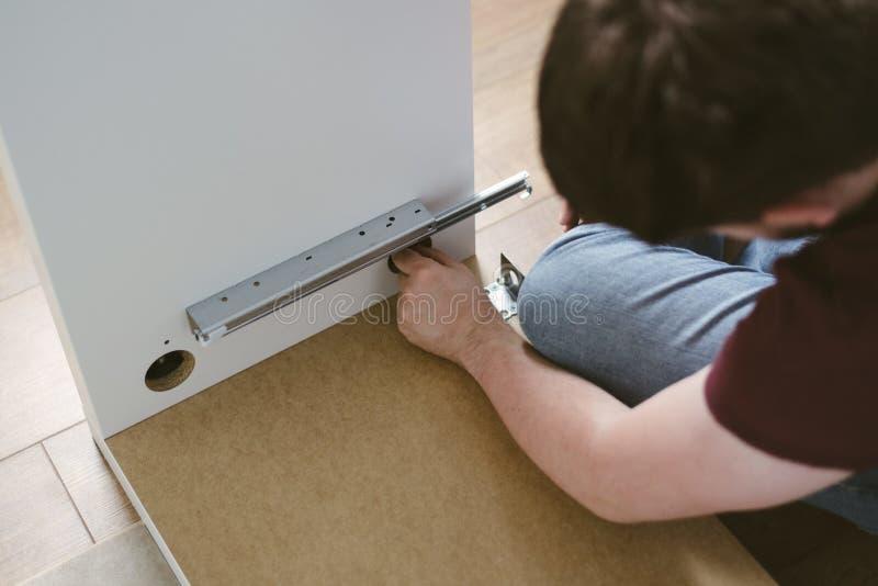 安装抽屉或架子的年轻白种人男性户内 免版税库存照片